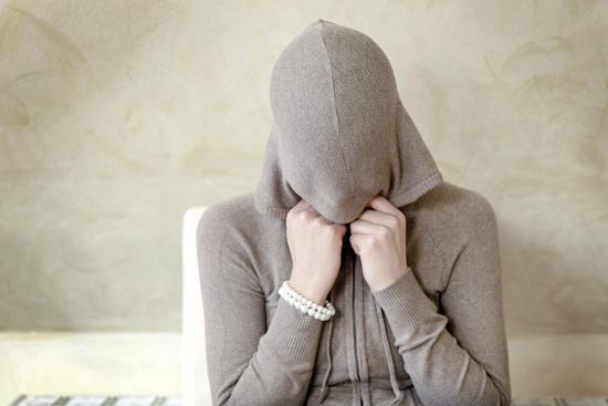 axel-schmies-teenage-girl-putting-on-hoodie-portrait