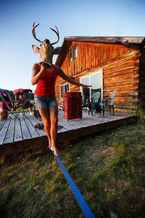 ben-herndon-a-woman-holds-a-mounted-deer-head-while-walking-a-static-line-at-sunset-in-north-idaho