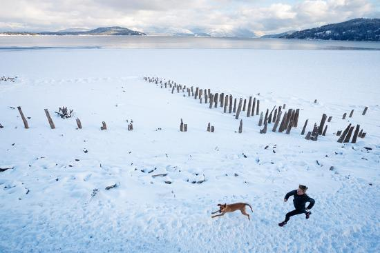 ben-herndon-noelle-zmuda-and-her-dog-tink-go-for-a-cold-winter-run-on-pond-oreille-bay-trail-sandpoint-idaho