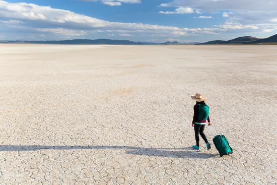 ben-herndon-traveler-rolls-a-carry-on-suitcase-the-playa-in-the-alvord-desert-of-se-oregon