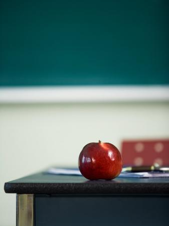 bright-red-apple-on-desk-of-teacher-in-classroom