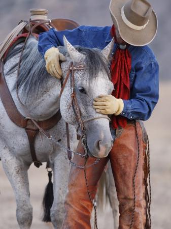 carol-walker-cowboy-leading-and-stroking-his-horse-flitner-ranch-shell-wyoming-usa
