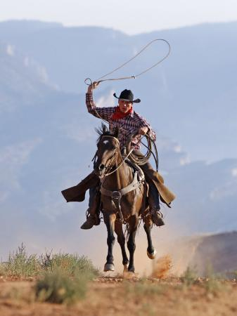 carol-walker-cowboy-running-with-rope-lassoo-in-hand-flitner-ranch-shell-wyoming-usa