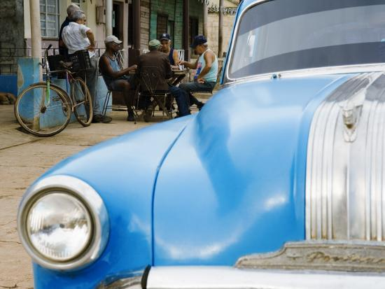 christian-aslund-vintage-car-and-cuban-men-playing-domino-game-on-marti-street