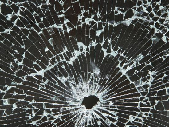 close-up-of-a-hole-in-cracked-and-shattered-glass