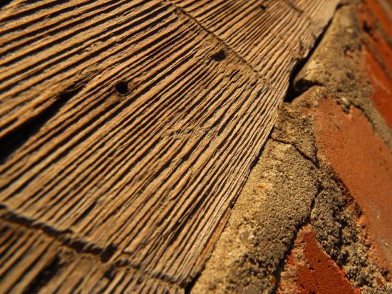 close-up-of-rough-wooden-surface-with-brick-and-grains-of-wood-visible
