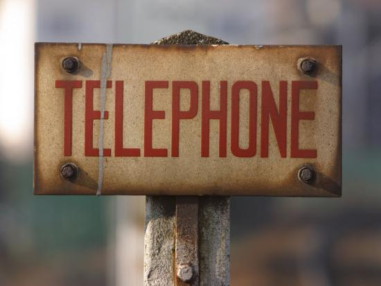 close-up-of-singed-telephone-sign-outdoors