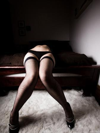 conceptual-image-of-lower-half-of-body-of-woman-wearing-lingerie-and-fishnet-stockings