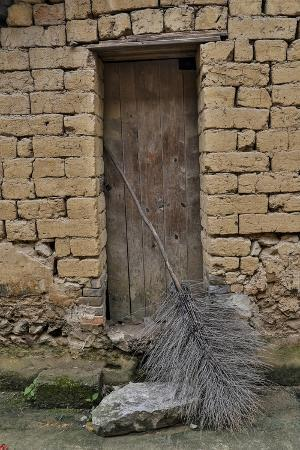 darrell-gulin-old-doorway-traditional-village-of-xingping-with-broom-in-front