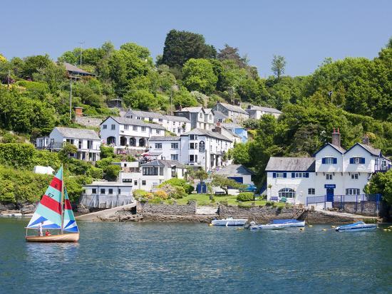 david-clapp-a-dinghy-sails-past-the-village-of-boddinick-near-fowey-cornwall-england-united-kingdom-europe