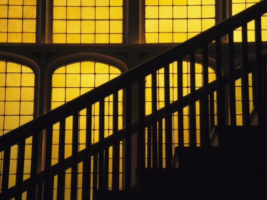 david-evans-a-staircase-in-silhouette-against-a-yellow-stained-glass-window