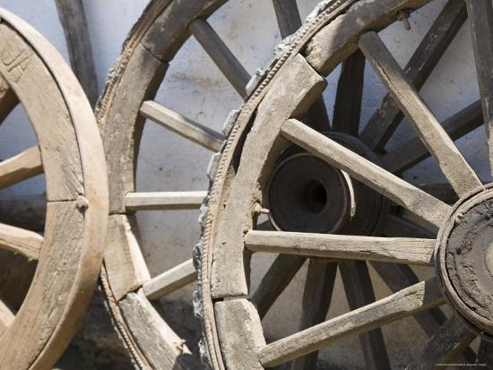 david-evans-old-wooden-wagon-wheels-leab-against-a-whitewashed-wall