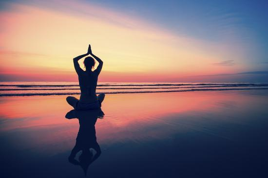 de-visu-woman-practicing-yoga-on-the-sea-beach-at-surrealistic-sunset