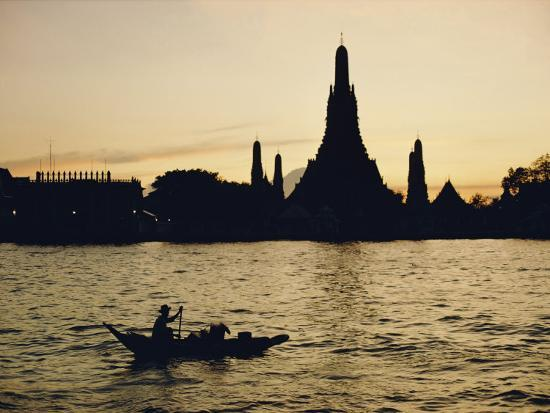 dean-conger-a-man-paddles-a-boat-past-wat-arun-at-twilight