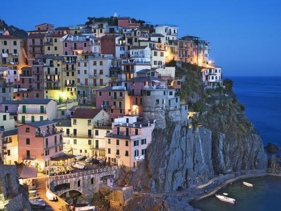 dennis-flaherty-dusk-falls-on-a-hillside-town-overlooking-the-mediterranean-sea-manarola-cinque-terre-italy