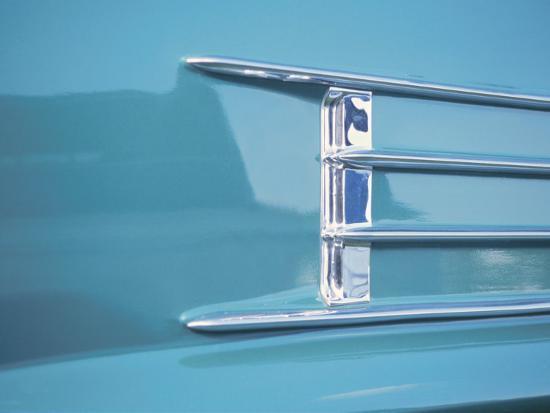 detail-of-a-shiny-chrome-decoration-on-a-vintage-blue-car