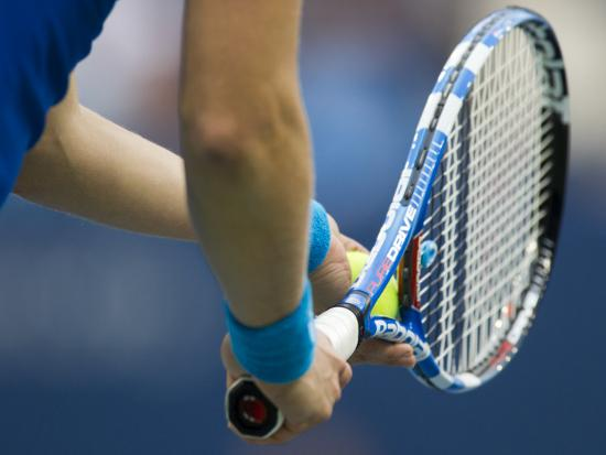 detail-of-tennis-player-holding-the-racquet-and-ball-about-to-serve