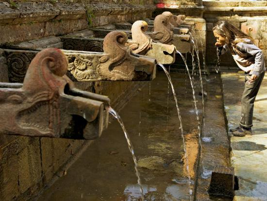 don-smith-girl-takes-a-drink-from-the-water-spouts-in-a-temple-courtyard-at-godavari-in-the-kathmandu-valley