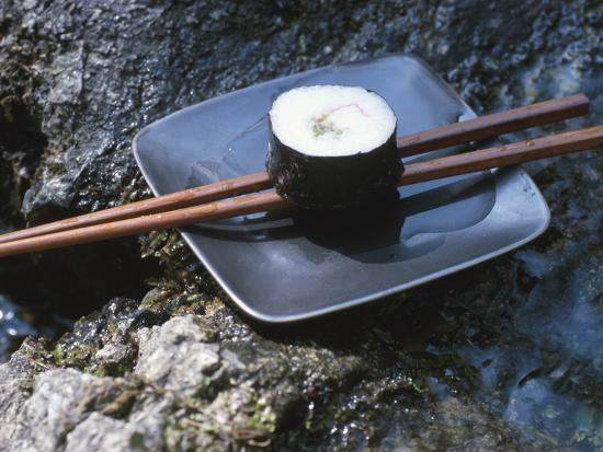 elegant-sushi-and-chopsticks-beside-rushing-water