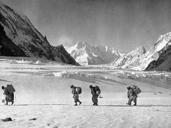 four-hunza-porters-on-the-way-towards-the-abruzzi-ridge-for-the-ascent-of-k2