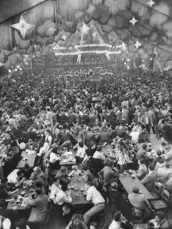 frank-scherschel-oktoberfest-drinking-beer-singing-dancing-tents-setup-for-drinking-band-under-canvas-clouds