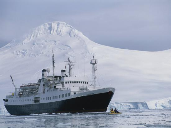 gordon-wiltsie-tourists-in-a-kayak-are-dwarfed-by-a-passenger-ship-off-anvers-island
