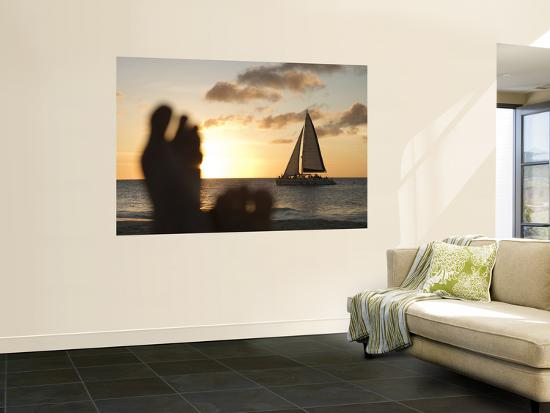 holger-leue-relaxing-feet-and-catamaran-at-sunset-seen-from-bucuti-beach-resort-on-eagle-beach