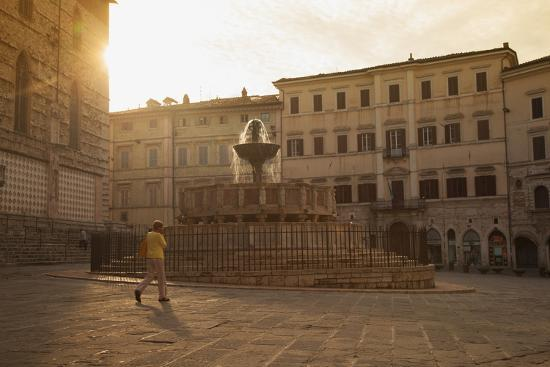 ian-trower-woman-walking-past-fontana-maggiore-in-piazza-iv-novembre-at-dawn-perugia-umbria-italy