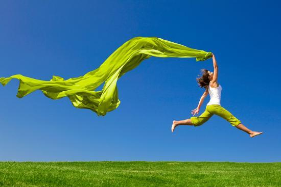 iko-beautiful-young-woman-jumping-on-a-green-meadow-with-a-colored-tissue