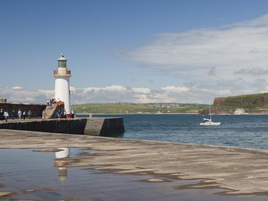 james-emmerson-lighthouse-at-entrance-to-outer-harbour-motor-yacht-entering-whitehaven-cumbria-england-uk