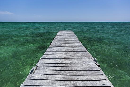 james-white-a-wood-dock-in-the-foreground-with-clear-green-water-and-blue-skies-near-the-isle-of-youth-cuba