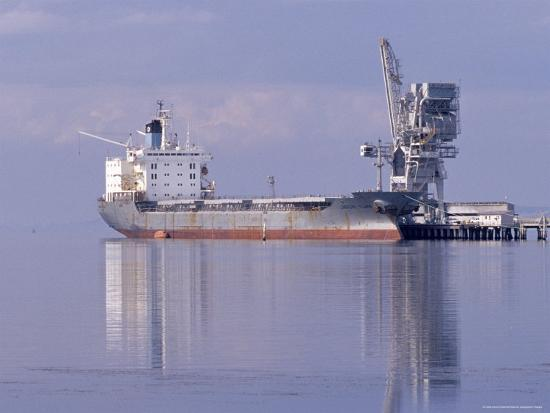 jason-edwards-cargo-tanker-ship-tied-up-to-a-jetty-reflecting-in-the-calm-harbour-australia