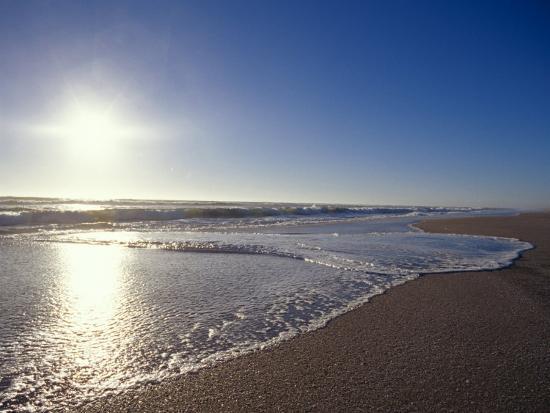 jason-edwards-gentle-waves-lap-onto-a-pristine-sandy-beach-with-the-sun-reflecting-australia