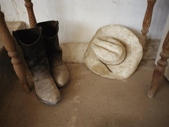 jodi-cobb-cowboy-boots-and-hat-lie-under-a-table