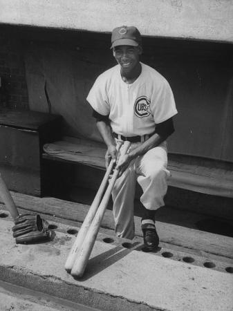 john-dominis-chicago-cub-s-ernie-banks-stooping-in-the-dug-out-holding-two-bats-against-cincinnati-reds