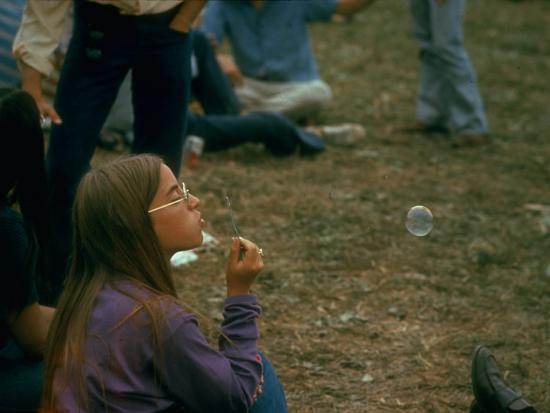 john-dominis-jackie-barg-sitting-on-the-ground-and-blowing-bubbles-during-the-woodstock-music-and-art-fair