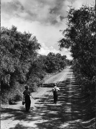 john-dominis-two-children-walking-down-a-dirt-road-going-fishing-on-a-summer-day