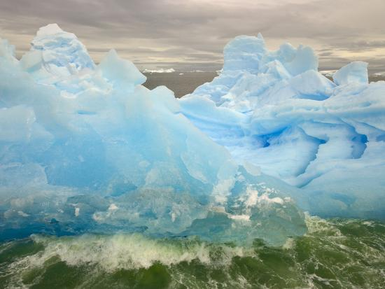 john-eastcott-yva-momatiuk-waves-lapping-against-iceberg-at-the-antarctic-peninsula