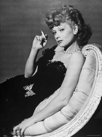 john-florea-dancer-actress-lucille-ball-in-strapless-black-lace-evening-dress-holding-lit-cigarette-on-couch