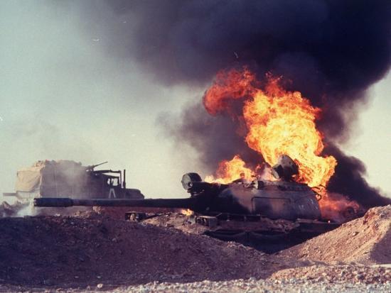 ken-jarecke-iraqi-tank-burning-while-us-army-convoy-drives-past-into-iraq-during-gulf-war