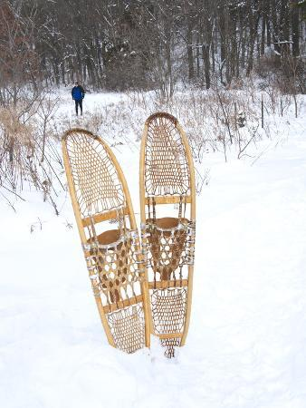 kimberly-walker-snowshoes-sticking-out-of-snow-with-skiier-in-background-minnesota-united-states-of-america-nort