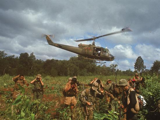 larry-burrows-american-uh1-huey-helicopter-lifting-off-as-personnel-on-the-ground-protect-themselves