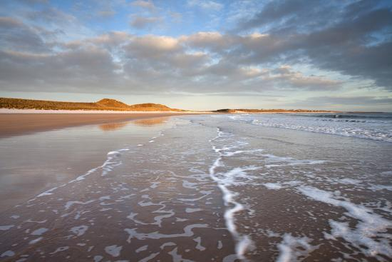 lee-frost-looking-across-embleton-bay-just-after-sunrise-towards-the-sunlit-sand-dunes