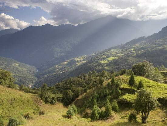 lee-frost-storm-light-bathing-tshankha-village-against-a-dramatic-backdrop-of-mountains-phobjikha-valley-bh
