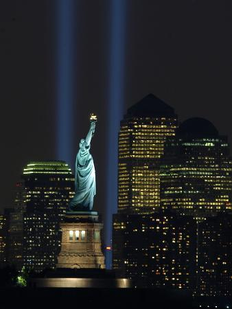 lights-from-the-former-world-trade-center-site-can-be-seen-on-both-sides-of-the-statue-of-liberty
