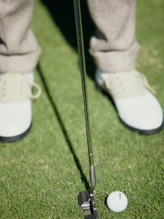 low-section-view-of-a-man-putting-a-golf-ball