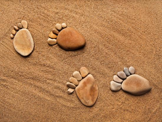 madlen-trace-feet-steps-made-of-a-pebble-stone-on-the-sea-sand-backdrop