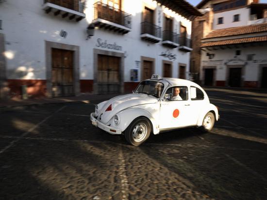 man-driving-a-volkswagen-taxi-plaza-borda-taxco-guerrero-mexico