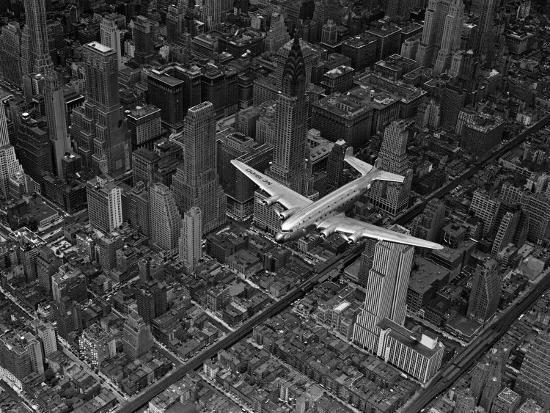 margaret-bourke-white-aerial-view-of-a-dc-4-passenger-plane-flying-over-midtown-manhattan