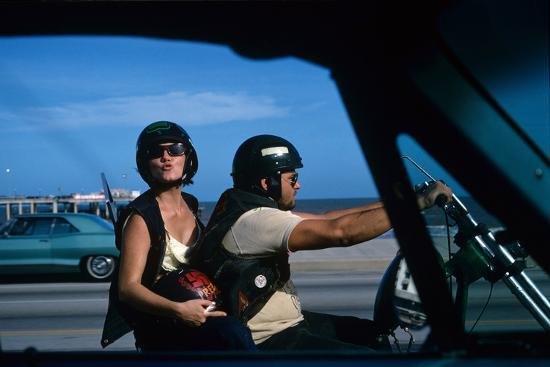 mario-de-biasi-a-young-biker-sitting-on-the-motorbike-saddle-with-his-companion